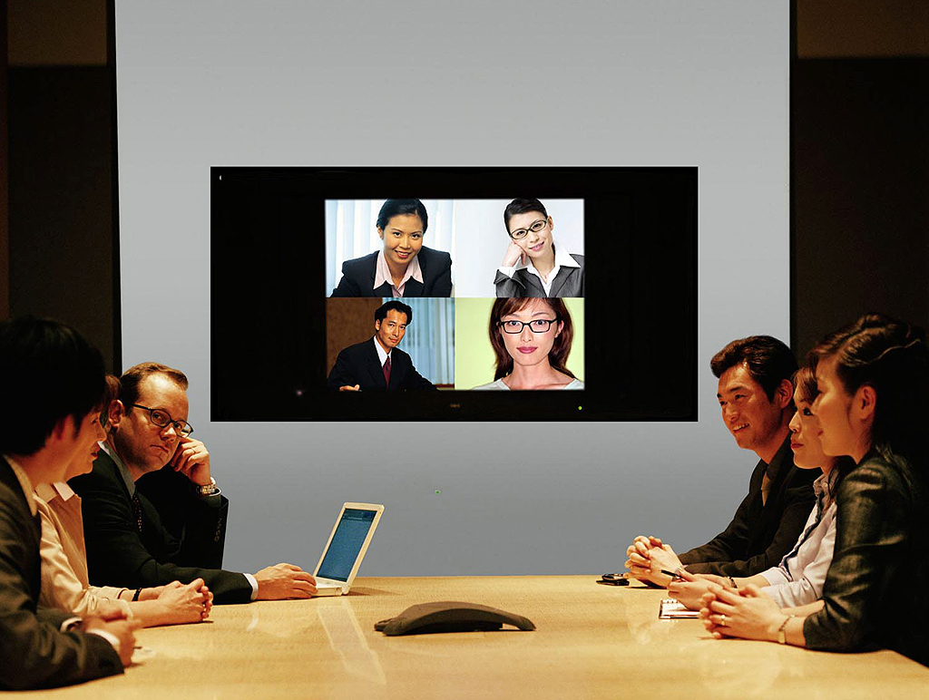 Businesspeople seated around conference table and monitor